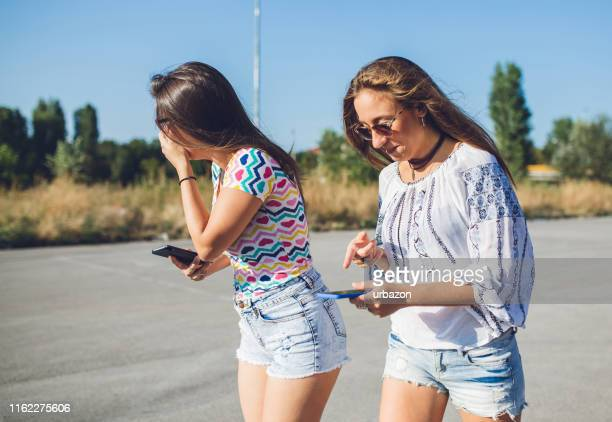 two girls using phones downtown - downtown comedy duo stock pictures, royalty-free photos & images