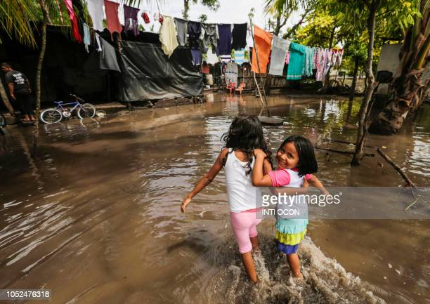 TOPSHOT Two girls wade towards their house through a flooded street following heavy rains in Tepalon Granada some 80 km east of Managua on October 18...