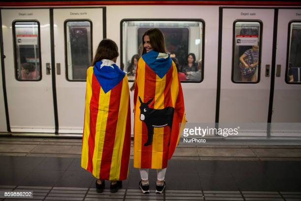 Two girls wait to get into the metro as they are wrapped with the Catalonian flag in Barcelona Spain Tuesday Oct 10 2017 Catalan President Puigdemont...