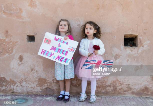 Two girls wait to meet Prince Harry Duke of Sussex and Meghan Duchess of Sussex visit the Andalusian Gardens to hear about youth empowerment in...