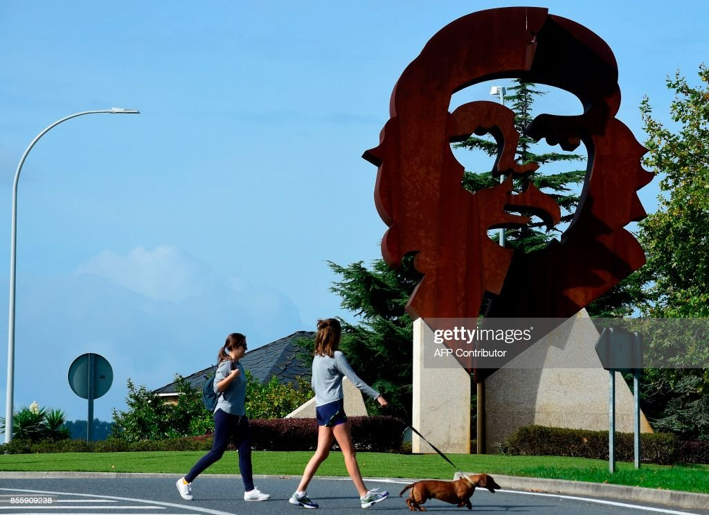 Two girls walk a dog past a monument dipicting the image of late Argentinian revolutionary legend Ernesto 'Che' Guevara, in Oleiros, some 10 km from Coruna, northwestern Spain on September 29, 2017. /