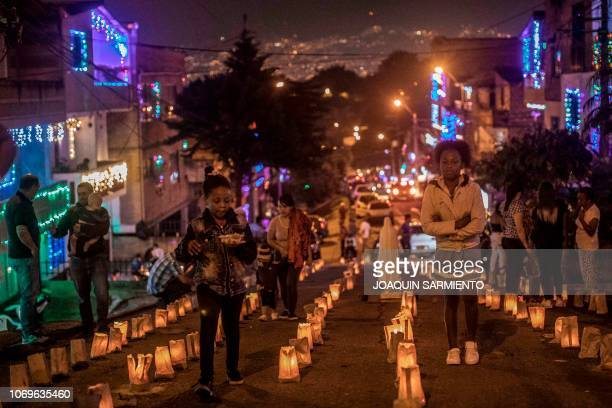 Two girls walk by candles on the Day of the Little Candles in Medellin Colombia on December 7 2018 The Day of the Little Candles is a traditional...