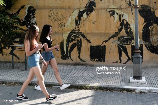Two girls walk past a graffity in Nea Pella, Central Macedonia, best known as the historical capital of the ancient Greek kingdom of Macedon and...
