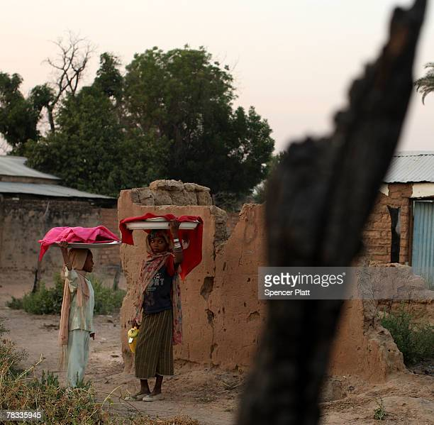 Two girls walk past homes that were burned in fighting December 8 2007 in Birao in northern Central African Republic After a peace agreement between...