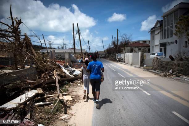 TOPSHOT Two girls walk past rubbles on September 11 2017 in GrandCase on the French Caribbean island of SaintMartin after it was hit by Hurricane...