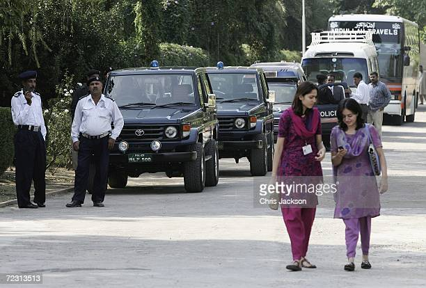 Two girls walk past security in place for the Royal visit to Fatima Jinnah Womens University of the third day of the Royal Tour of Pakistan on...