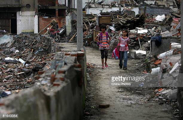 Two girls walk through the debris of damaged buildings at the Yinghua Township on June 19, 2008 in Shifang of Sichuan Province, China. More than...