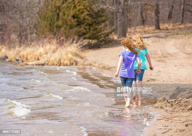 Two Girls Walking Along Beach in Early Springtime