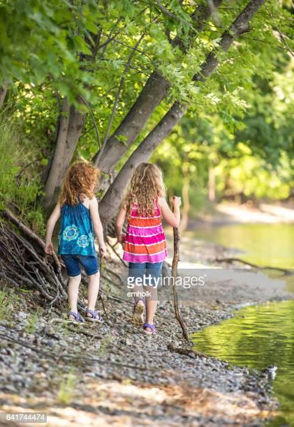 Two Girls Walking Along Mississippi River Bank