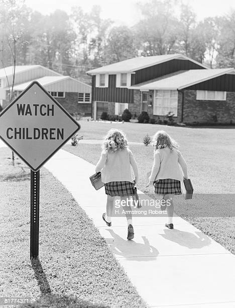 Two girls walking along suburban street. (Photo by H. Armstrong Roberts/Retrofile/Getty Images)