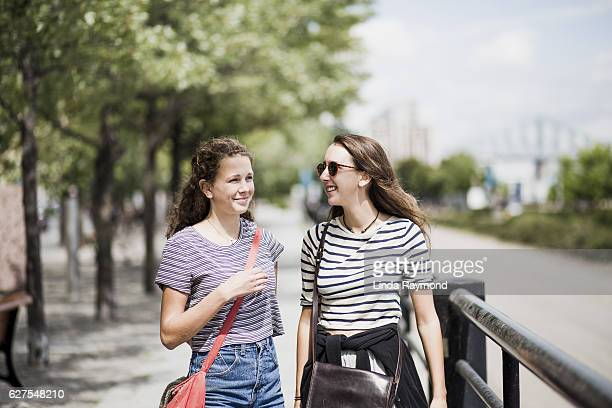 two girls walking and talking in old montreal - vieux montréal stock pictures, royalty-free photos & images
