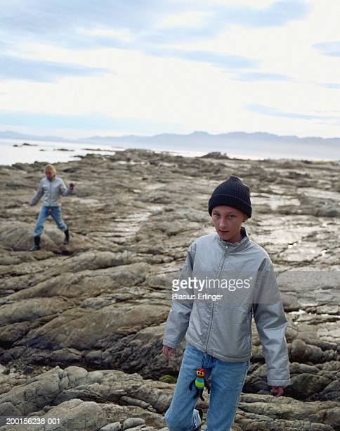two girls (9-11) walking on rocky beach - blasius erlinger stock pictures, royalty-free photos & images