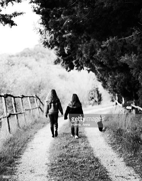 Two girls walking with a cat on a graveled road, Italy.