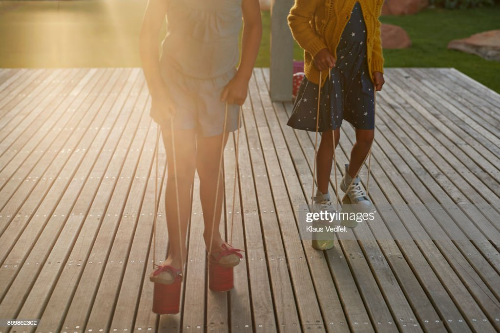 Two Girls Walking With Can Stilts On Wooden Terrace : Stock Photo