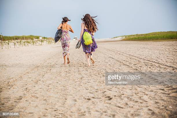 two girls walks at the jones beach at the sunset - jones beach stock pictures, royalty-free photos & images