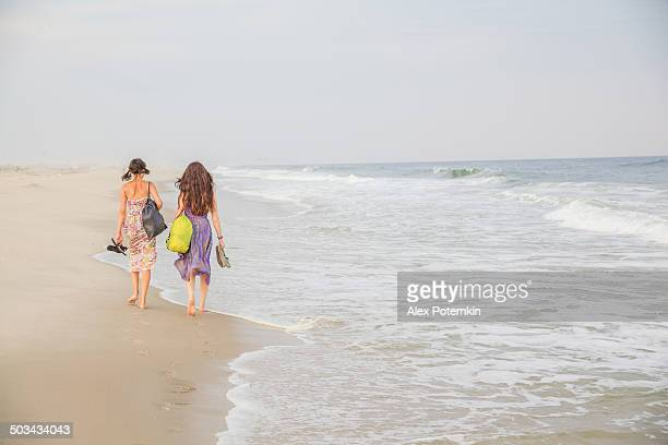 Two girls walks at the Jones Beach at the sunset