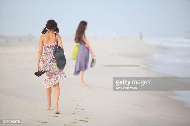 two girls walks at the jones beach at the sunset - wantagh stock pictures, royalty-free photos & images