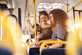 Two girls watching phone and smiling while standing on a bus.