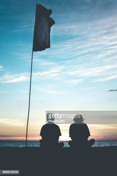 two girls watching sunset under a flag - drappo bianco foto e immagini stock