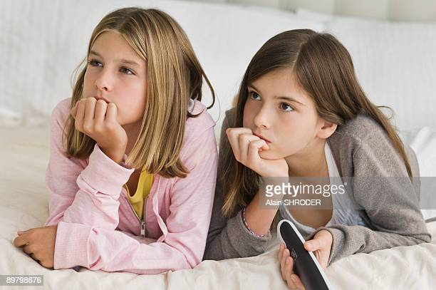 Two girls watching television