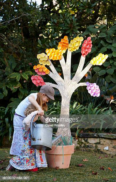 Two girls (12-17 months) watering paper plant in garden