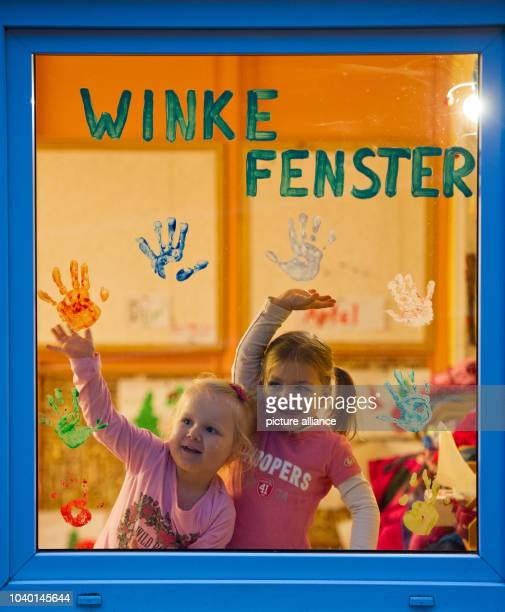 Two girls wave at the 'WinkeFenster' of kindergarten Matroschka in Frankfurt Oder Germany 06 December 2013 Children can wave to their parents from...