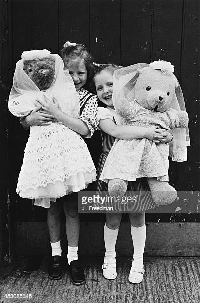 Two girls wear dresses and carry teddy bears on their way to their First Communion Ireland 1973