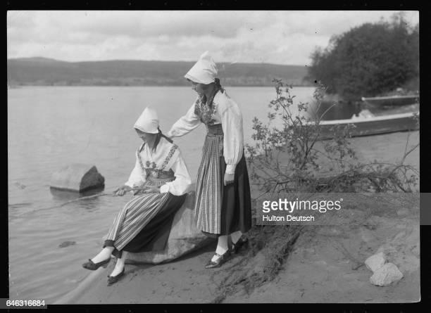 Two girls wear the Swedish national costume.