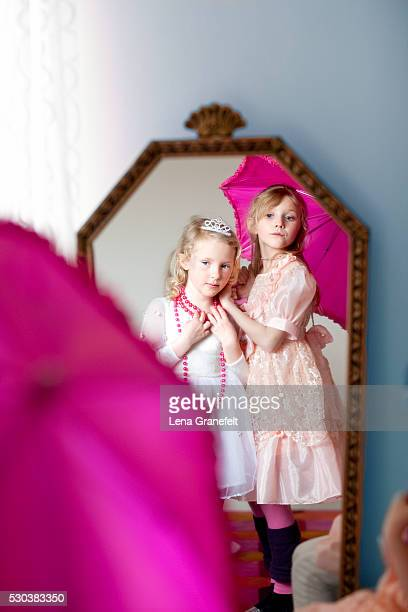 two girls wearing elegant dresses and necklaces looking in mirror - girl in mirror stock photos and pictures