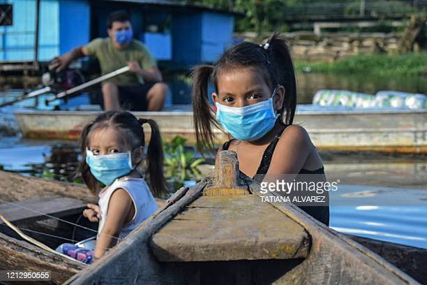 Two girls wearing face masks, as a preventive measure against the spread of the novel coronavirus, COVID-19, sail at the Amazon river in Leticia,...