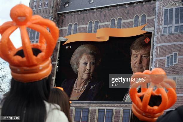 Two girls wearing orange plastic crowns watch King Willem Alexander and Queen Beatrix broadcastt on giant screen at the Dam square during the Queen's...
