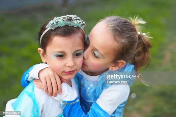two girls wearing princess dresses kissing - royal person stock pictures, royalty-free photos & images