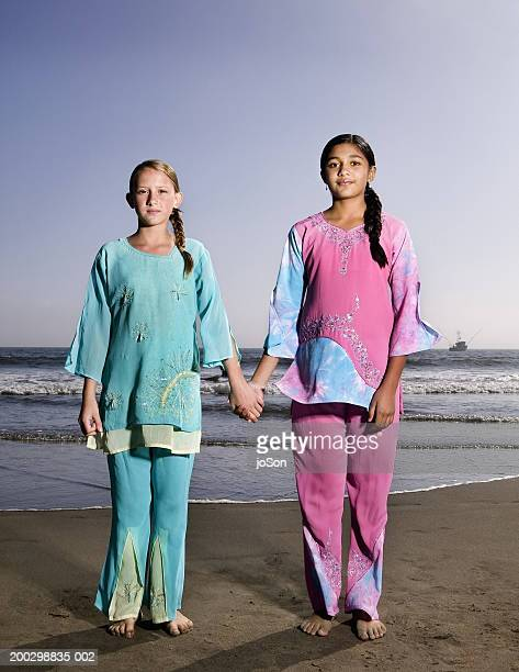 Two girls (10-13) wearing saris at beach, holding hands