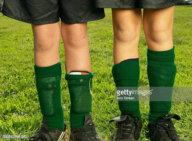 Two girls (10-12) wearing soccer uniforms, low section