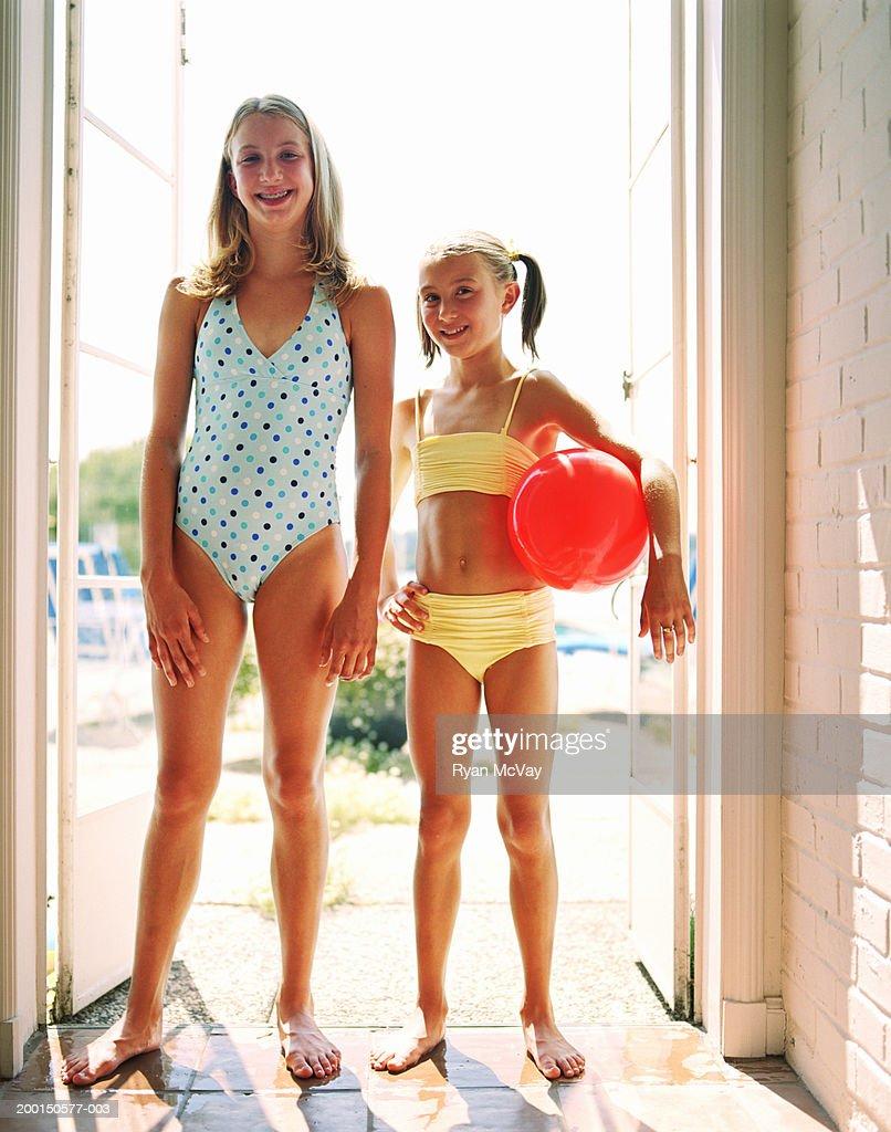Two girls (9-12) wearing swimsuits, standing in doorway, portrait : Stock Photo