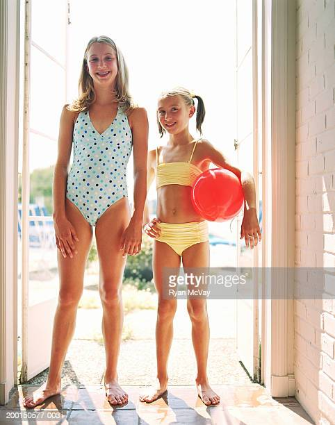 two girls (9-12) wearing swimsuits, standing in doorway, portrait - swimwear stock photos and pictures