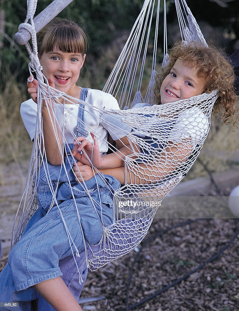 two girls wearing white shirts and denim overalls sit in a hammock smiling : Stockfoto