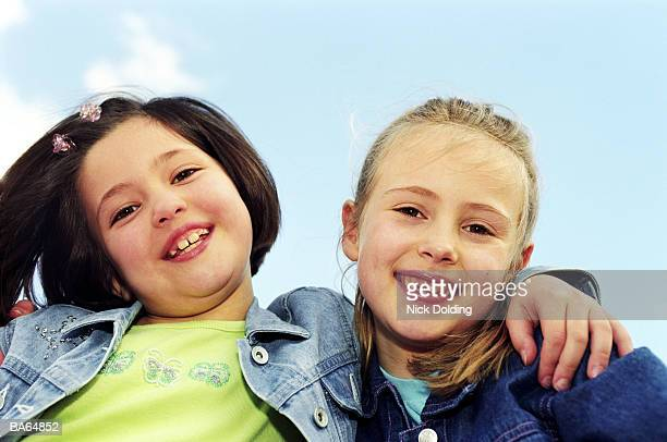 Two girls with arms around each other, portrait, close-up