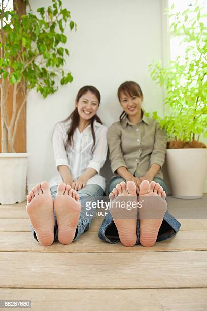 Two girls with bare feet siiting on the floor.