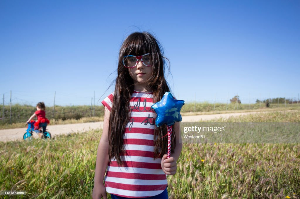 Two girls with bicycle and star-shaped wand in remote landscape : Stock Photo