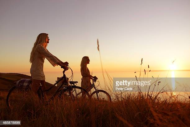 Two girls with bikes watching sunset over sea