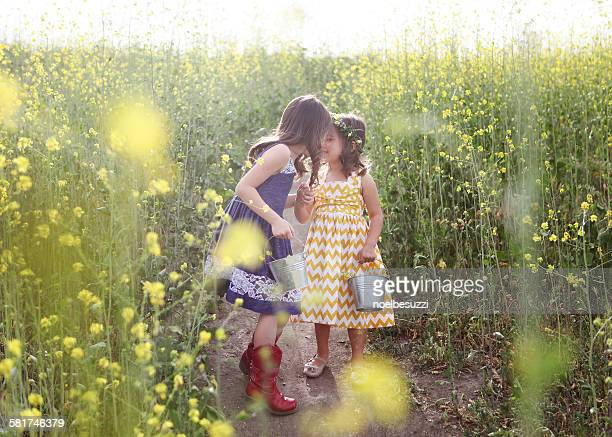 Two girls with buckets picking flowers