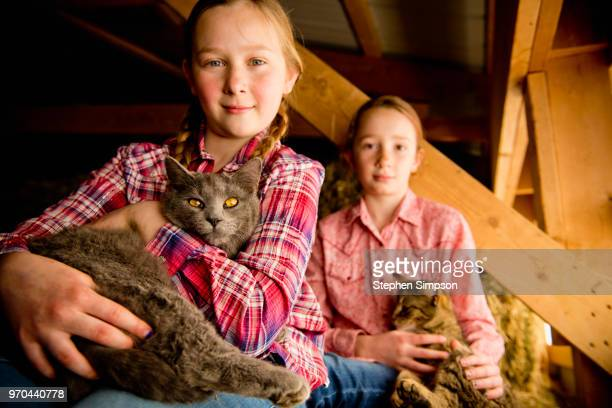 Two girls with cats in a barn in Montana