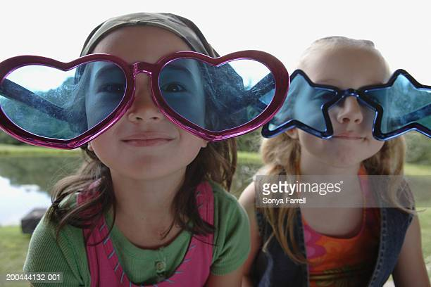 Two girls (5-7) with heart and star shaped glasses, portrait, close-up