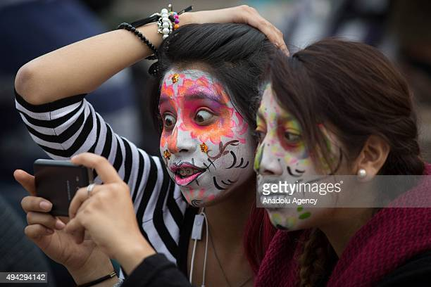 Two girls with make up take selfie during Procession of the Catrinas in Mexico City Mexico on October 25 2015 The Catrina is a figure of a skeleton...