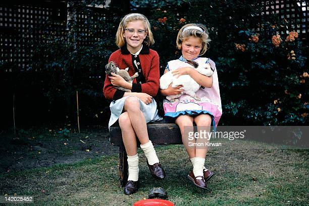 Two girls with pet rabbits