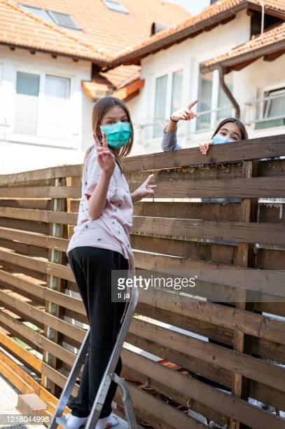 deux filles avec le masque protecteur parlant au-dessus de la haute barrière en bois - éviter de se serrer la main photos et images de collection