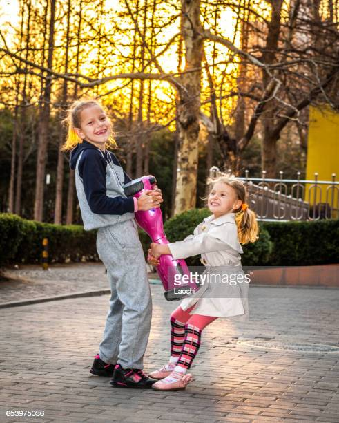 twee meisjes met segway - hoverboard stockfoto's en -beelden