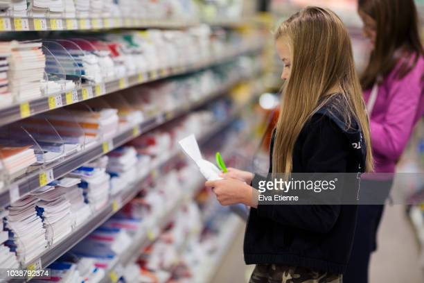Two girls with shopping list looking for 'back to school' stationery in a store