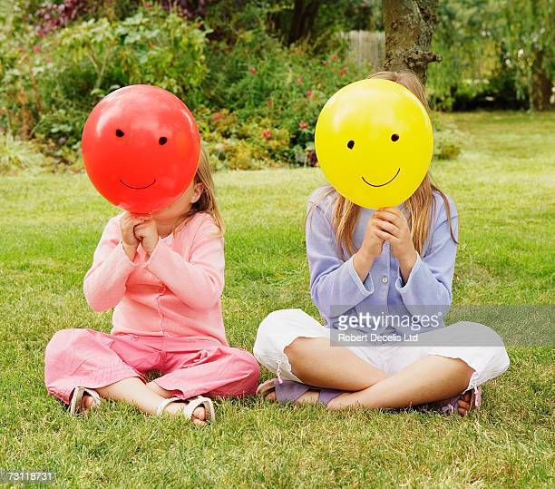 Two girls (5-8) with smiley face balloons covering heads in garden